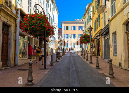 People walking on narrow street decorated with flowers in Old Town of Antibes, France. - Stock Photo