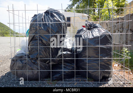Black garbage bag garbage dump, bin,trash, garbage, rubbish, plastic bags pile background , Cage garbage bin with black garbage bags. - Stock Photo