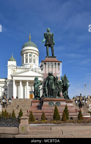 Statue of Emperor Alexander II of Russia and Finnish Evangelical Lutheran cathedral of Diocese of Helsinki - Stock Photo