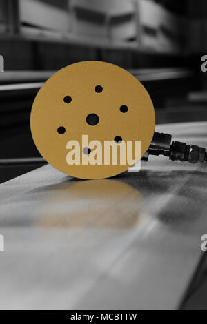 Orbital air sander with a sanding disc attached on a metal panel with selective color - Stock Photo