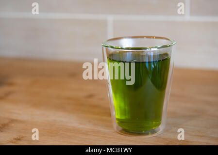 Green Tea cup and glass jugs or jars on the wooden table. - Stock Photo