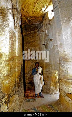 Orthodox priest standing inside a rock corridor in the rock-hewn church Medhane Alem, Tigray region, Ethiopia - Stock Photo
