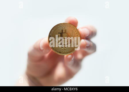 Golden bitcoin coin in man hand closeup - Stock Photo