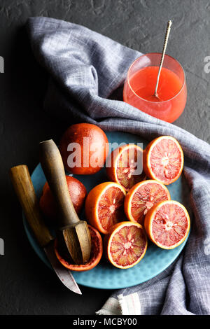 Red sicilian orange pieces on blue plate closeup - Stock Photo