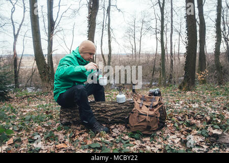 Man with backpack in wild forest - Stock Photo