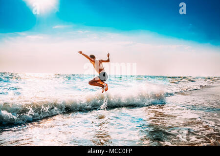 Boy Having Fun And Jumping In Sea Ocean Waves. Jump Accompanied By Water Splashes. Summer Sunny Day, Ocean Coast, Beach. Active Lifestyle And Recreati - Stock Photo