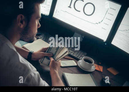 Successful investor holding cash making money with initial coin offering, rich stock trader broker earned high profit from cryptocurrency investment,  - Stock Photo