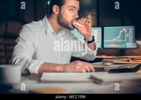Busy businessman having late lunch eating sandwich in office working at night, stock broker trading online and eating snack looking at computer, workp - Stock Photo