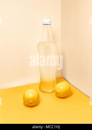 Lemonade in bottle Transparent glass bottle with lemonade and two whole lemons near are standing against light wall Trendy photo mockup with copy spac - Stock Photo