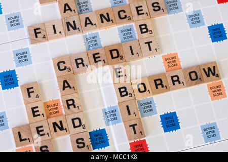 A series of words on a scrabble board relating to finances and debt - Stock Photo