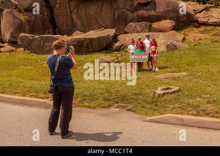 Gettysburg, PA, USA - July 8, 2013:  Visitors pose for a photo at Devil's Den on the Gettysburg battlefield. - Stock Photo