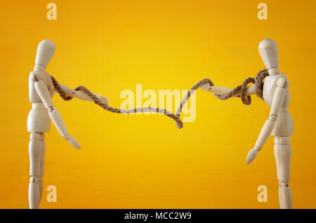 Competition concept. two wooden people pull rope symbol of rivalry, conflict. and dillema - Stock Photo