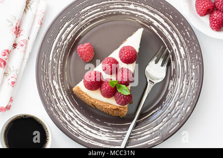Top view of cheesecake slice with fresh raspberries on white background, selective focus - Stock Photo