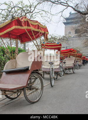 Rickshaw's park in the early morning around the famous Bell tower in Beijing, China - Stock Photo
