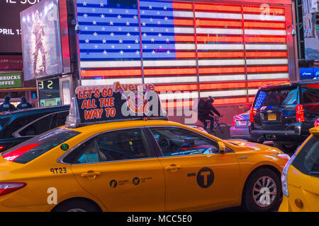 Yellow cab speeds past giant neon US flag on New York City's Times Square, April 2018 - Stock Photo