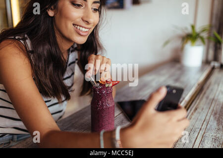 Woman taking a selfie with a smoothie using a mobile phone for her food blog. Food blogger shooting photos for her blog at home. - Stock Photo