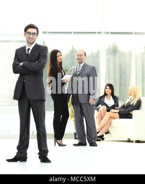 young businessman standing in the center of the modern office - Stock Photo
