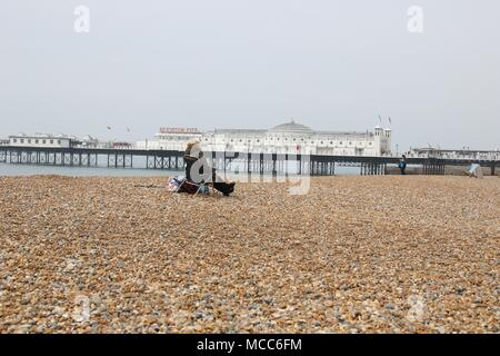 rear view of a woman sitting on a deckchair on a deserted beach with Brighton pier in the background on an overcast day. - Stock Photo