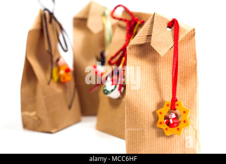 four brown gift bags with decorations isolated on white background - Stock Photo