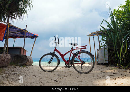 Red off-road bike stands in the sand on the beach against the sea. Tourist entertainment on the island. Riding a bike. Light tinted photo. Bicycle par - Stock Photo