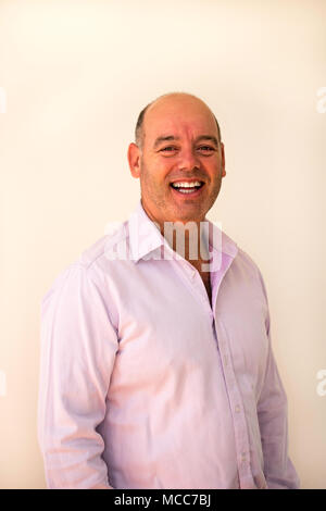 A slightly overweight businessman dressed in business casual clothes with no tie - Stock Photo