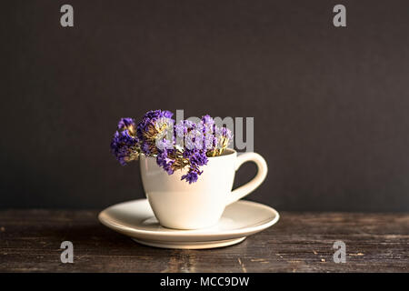 Dried flowers in a white coffee cup and placed on a wooden table.Warm tone photo. - Stock Photo