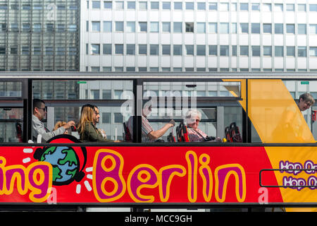 People sit on the top deck of one of the many 'Hop On, Hop Off' buses that are a major tourist attraction in the German capital of Berlin. - Stock Photo