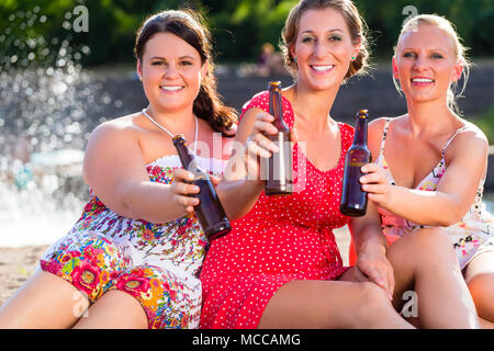 Friends drinking beer at river beach - Stock Photo