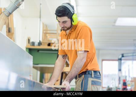 Carpenter working in furniture factory on machine - Stock Photo