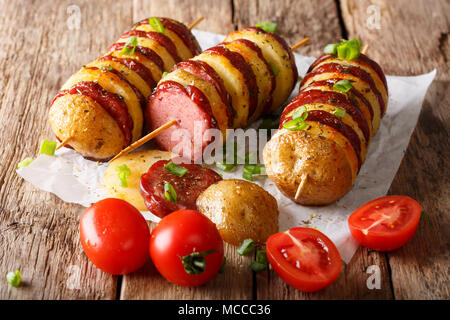 Freshly prepared shish kebab from potato skewers with sausage salami and tomatoes, green onions close-up on the table. horizontal