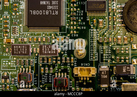 Close up view of motherboard showing main computer components and portals, microprocessors and intricate network of connections - Stock Photo