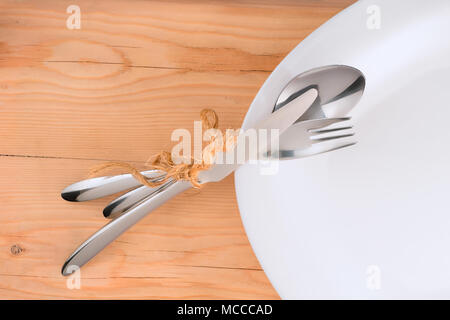 Place setting. Tied with rough rope cutlery on white plate. On wooden table background - Stock Photo