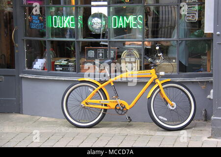 Yellow bicycle propped up against the Black Dog Hair Cutters Salon in Falmouth, Cornwall, England, UK, PETER GRANT - Stock Photo