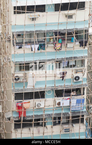 Builders repairing a building using traditional Indian wooden scaffolding made out of wood poles tied together with rope, Malabar, Mumbai, India - Stock Photo