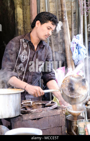 A man pouring masala chai (Indian tea) at a tea stall on Nagdevi street near Crawford market, Mumbai - Stock Photo