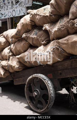 Over-laden hand cart with sacks full of charcoal on Nagdevi street near Crawford Market in Mumbai - Stock Photo