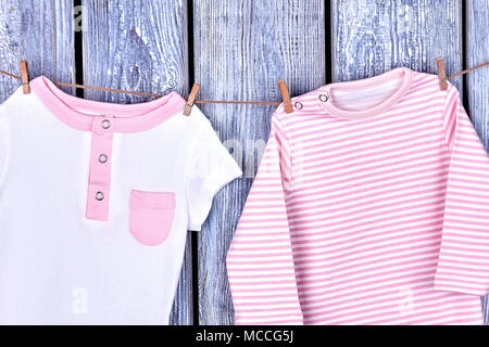909ada32335f ... Infant girl organic apparel on rope. Baby-girl cotton rompers hanging on  clothesline on