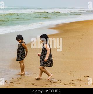 Twin Sisters indian kids running on puri sandy beach in seashore expressing joy. - Stock Photo