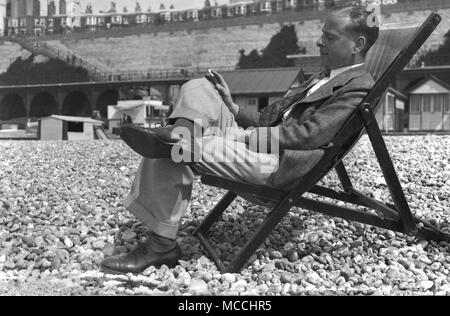 Late 1940s, historical, a well-dressed gentleman enjoying a cigarette and a nap - a little shut-eye - while relaxing on his own sitting in a deckchair outside on a pebbly beach, England, UK. - Stock Photo