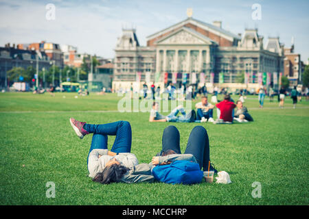 Relaxed couple on grass in public park with the VanGogh museum on the background, Amsterdam, Holland - Stock Photo