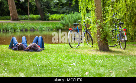 Relaxed couple on grass in public park after a bike riding, Vondelpark, Amsterdam, Holland - Stock Photo