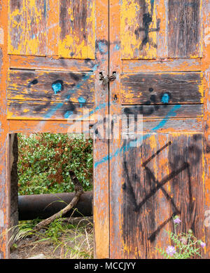 Flaking/peeling paint on old, weathered wooden door with swastika painted on door. - Stock Photo