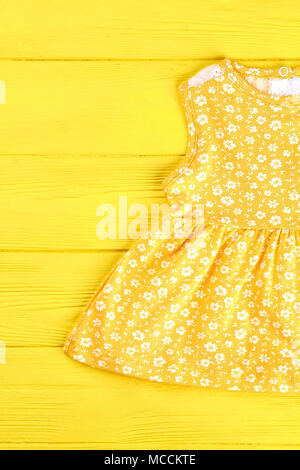 e4c539330cfd Baby-girl yellow printed top. Infant girl yellow patterned dress on yellow  wooden background
