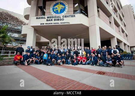 180210-N-IE405-1361 SAN DIEGO (Feb. 10, 2018) Wounded warriors, veterans, volunteers, and caregivers pose a group photo with Hollywood actor, musician, humanitarian, and honorary chief petty officer Gary Sinise at Naval Medical Center San Diego (NMCSD) during the sixth annual Invincible Spirit Festival. The festival also included activities for children, rock climbing, food cooked by Team Irvine and 149 volunteers who set up and served food at the event. Gary Sinise and Lt. Dan Band debut their first military concert at NMCSD in 2012. (U.S. Navy photo by Mass Communication Specialist 2nd Class - Stock Photo