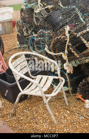 Old chair and lobster pots on the beach - Stock Photo