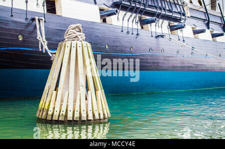 wooden mooring post in the water with ropes tied to the historic USS Constellation warship in Baltimore's Inner Harbor USA - Stock Photo