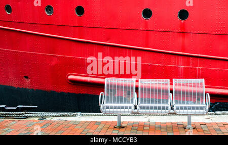 3 empty white metal chairs on a brick walkway in front of a large bright red ship's hull with portholes at Baltimore's Inner Harbor - Stock Photo