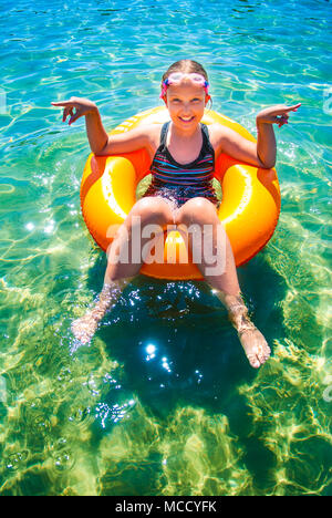 Young girl sitting and smiling in inflatable ring on water ocean. Summer vacations concept. - Stock Photo