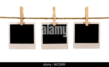 Several blank polaroid style instant photo print frames hanging on a rope or washing line, white background - Stock Photo