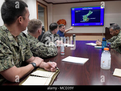 U.S. Coast Guard Lt. Cliff Graham, assigned to USCG, Sector Guam, explains the drift-current complications in a search area off the eastern coast of Guam during a table-top exercise designed to demonstrate interoperability for a joint search and rescue operation, Feb. 16, 2018. CTF 75 is the primary expeditionary task force responsible for the planning and execution of coastal riverine operations, explosive ordnance disposal, diving engineering and construction and underwater construction in the U.S. 7th Fleet area of operations. (U.S. Navy Combat Camera photo by Mass Communication Specialist  - Stock Photo